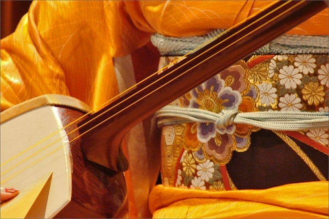 Shamisen © By Jean-Pierre Dalbéra from Paris, France - Fumie Hihara au shamisen (auditorium du musée Guimet), CC BY 2.0, Link